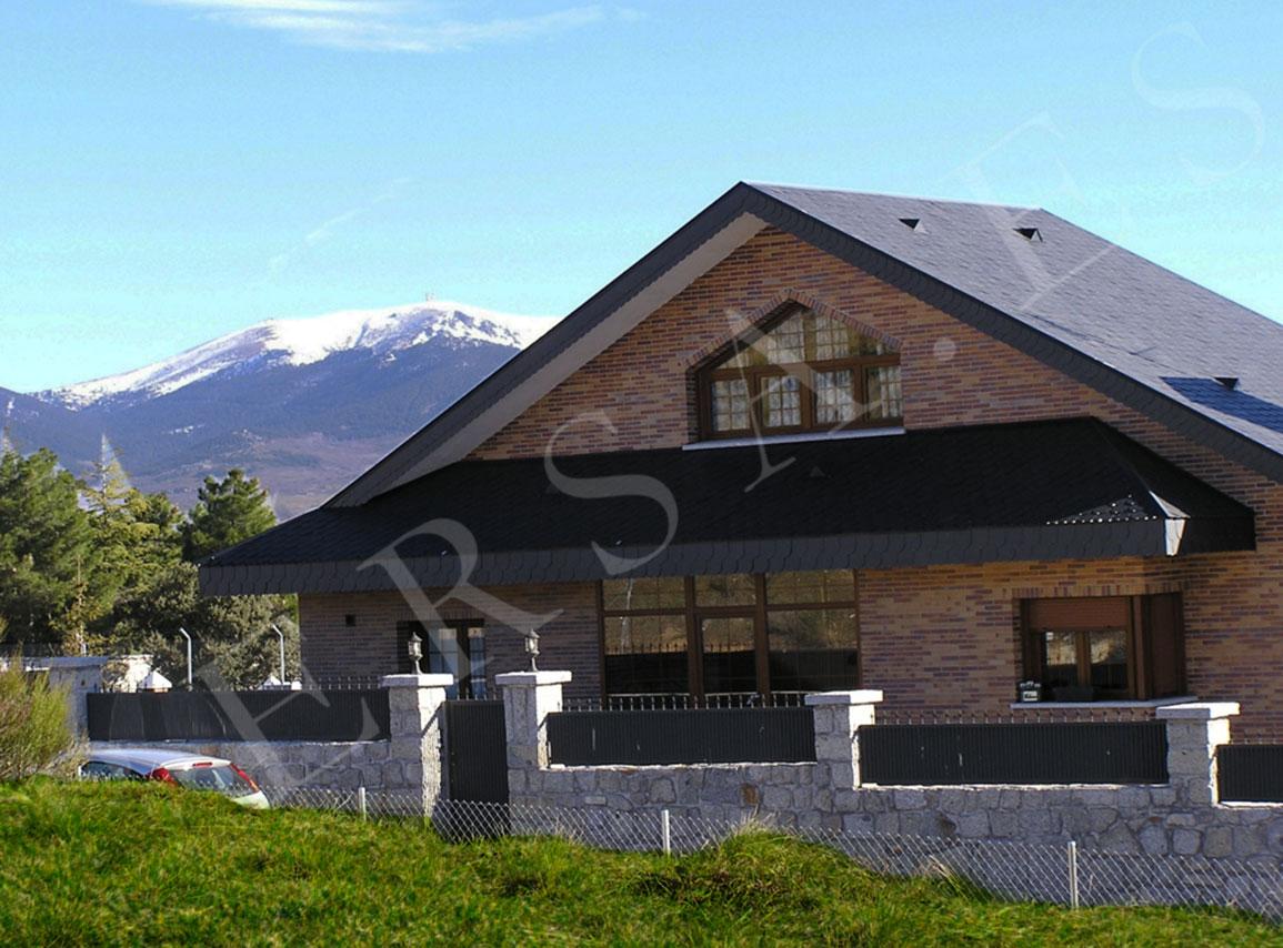 chalet con ventanas pvc marron y la sierra de guadarrama nevada