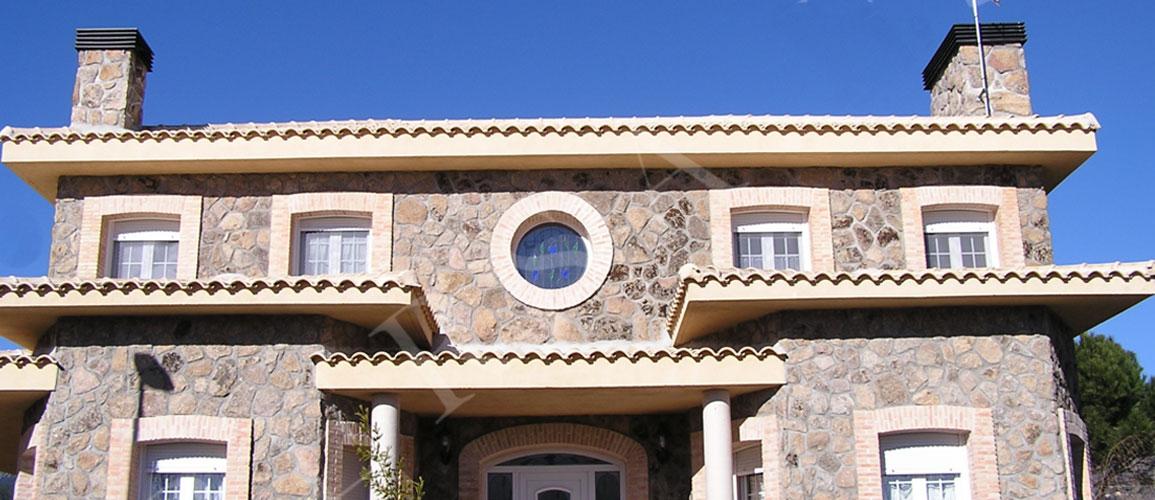 casa rustica de piedra grande con ventanas de pvc