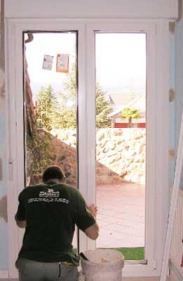 Acristalando y rematando la colocación de una ventana en pvc por un técnico de Bersa